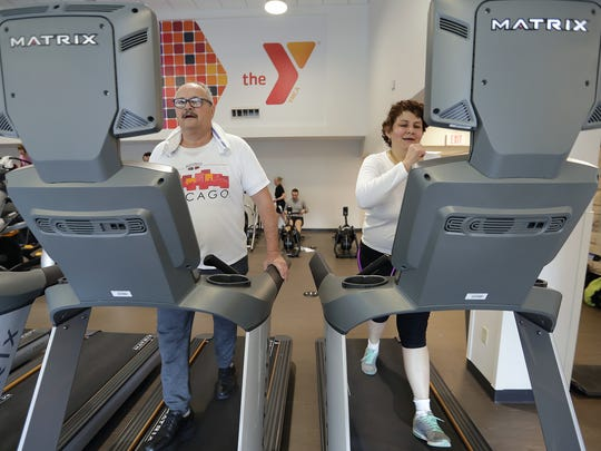 Lupita Romero and Jesus Zapata work out on the treadmills in the newly renovated Wellness Center at the Downtown Green Bay YMCA.