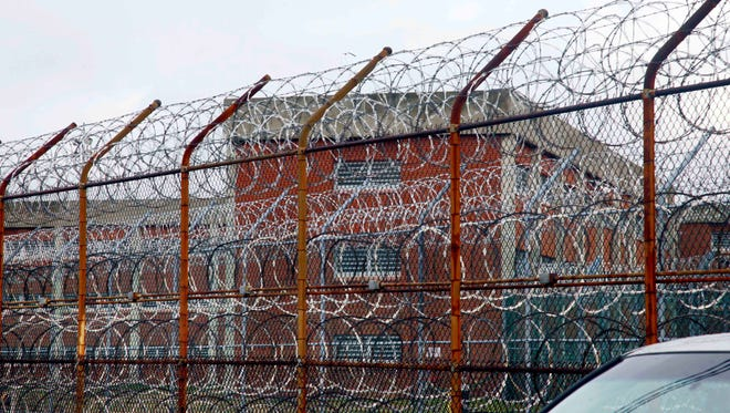 Inmate housing on New York's Rikers Island correctional facility can be seen on the other side of a fence topped with razor wire.