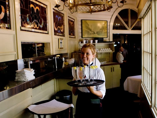 A bow-tie clad server brings a round of drinks to a table at The Veranda in Fort Myers.