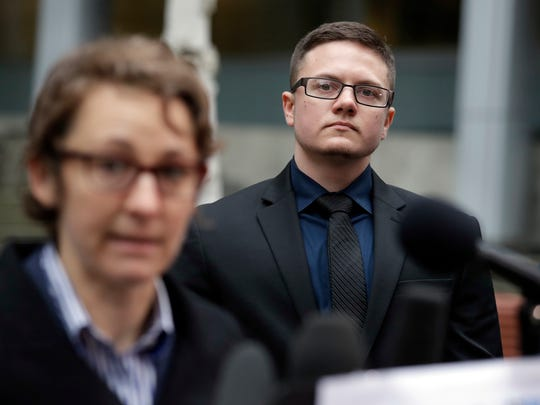 Plaintiff Conner Callahan, right, listens as attorney Natalie Nardecchia speaks to reporters after a hearing at the federal courthouse in Seattle on Tuesday. U.S. District Judge Marsha Pechman says she won't immediately consider President Donald Trump's new policy banning transgender people from serving in the military. Pechman is one of four federal judges who have issued orders blocking Trump's decision last year to overturn an Obama-era directive allowing transgender troops to serve openly.