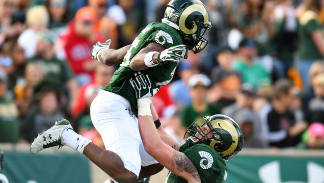 CSU running back Izzy Matthews celebrates one of his two touchdown runs Saturday with tackle Zack Golditch. The Rams beat Fresno State 37-0 at Hughes Stadium to improve to 5-4.