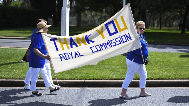 Members of the Care Leavers Australasia Network (CLAN) hold up a banner thanking the commission as they await the final report from the Royal Commission into Institutional Responses to Child Sexual Abuse outside Government House in Canberra, Australia, Dec. 15, 2017.