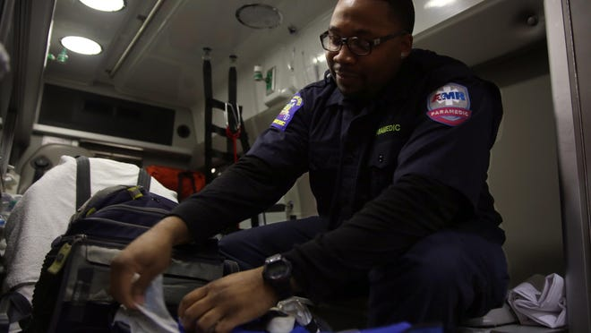 At the start of his shift, Edward Morrison does a rig check, making sure he has all the right supplies in the ambulance on Monday, Dec. 12, 2016.