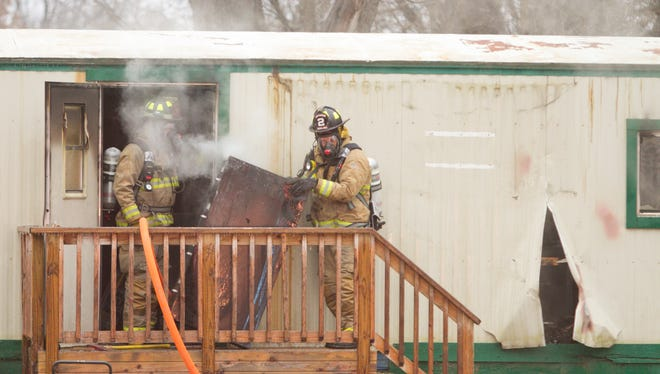 Firefighters carry out a smoking file cabinet from the office of Screeners Landscape Supply in Putnam Township. A fire in the trailer prompted response from Putnam, Hamburg and Howell fire departments.