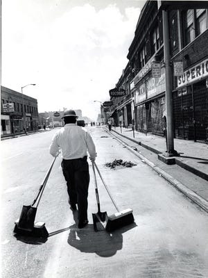 A man is seen cleaning up debris after the1967 Riots.