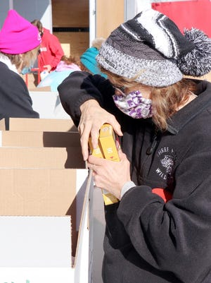 Volunteers pack food boxes at a fresh food distribution last month through St. Joseph County United Way in Centreville.
