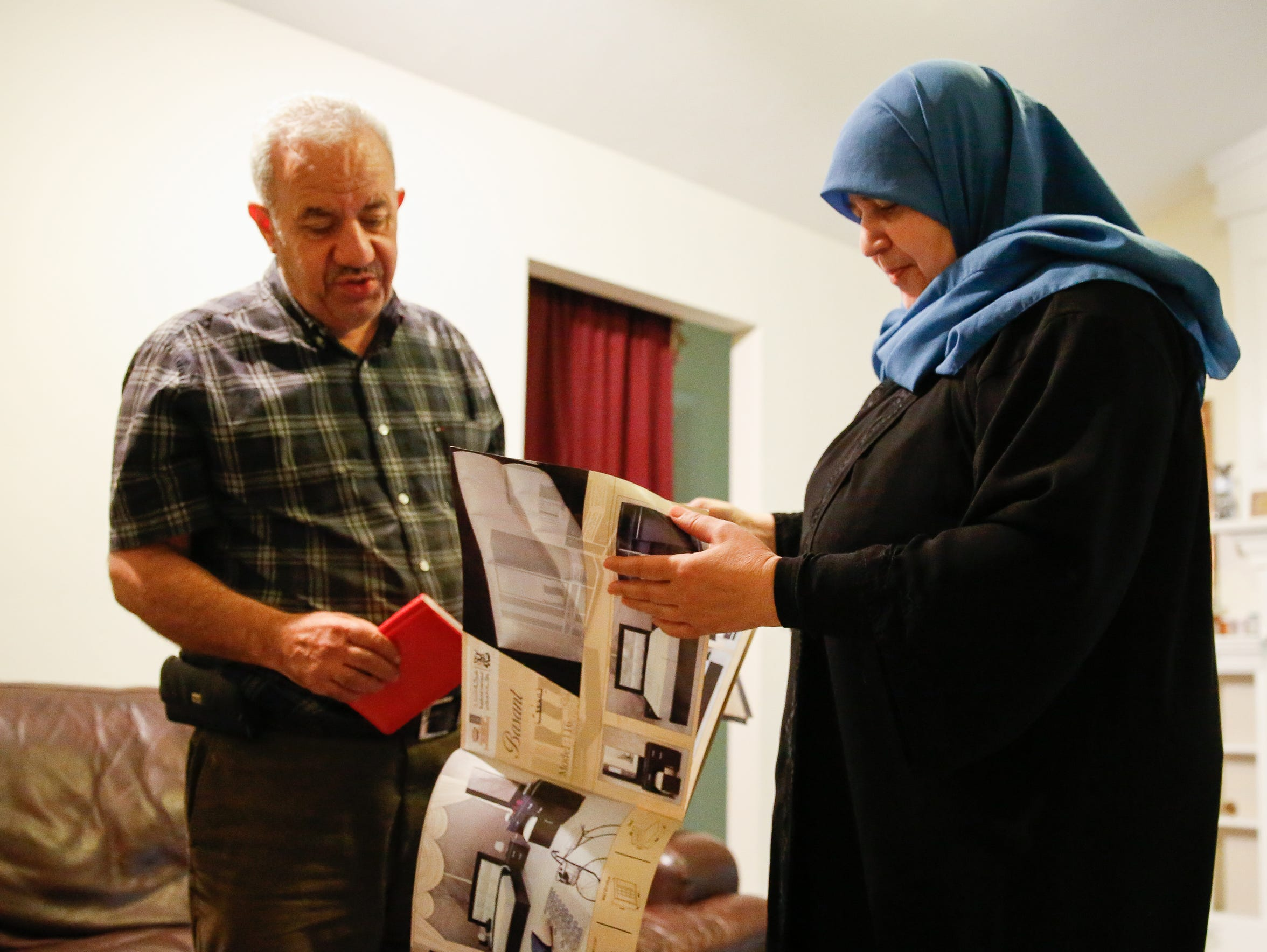 Bassam Alhalabi and his wife Osaima Alhalabi look through an archive of their family's furniture business located in Damascus, Syria. The Alhalabis had to close the business and flee Syria due to the country's ongoing civil war.