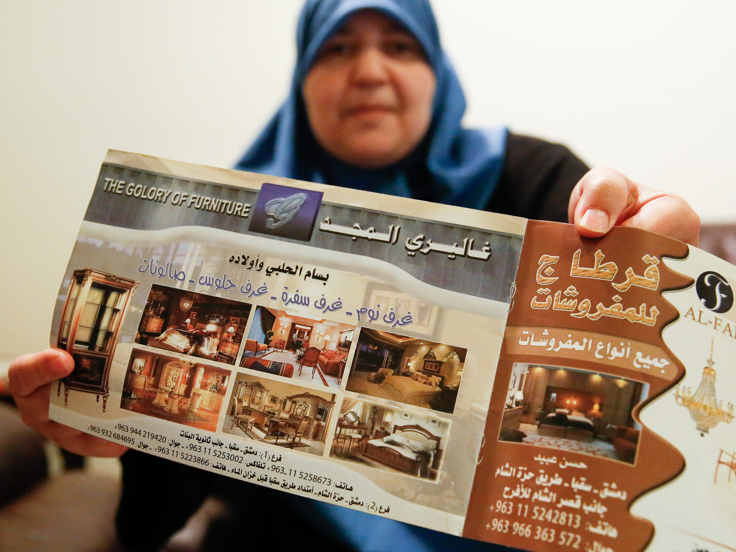 Osaima Alhalabi shows an old advertisement for her family's business back in Damascus, Syria.