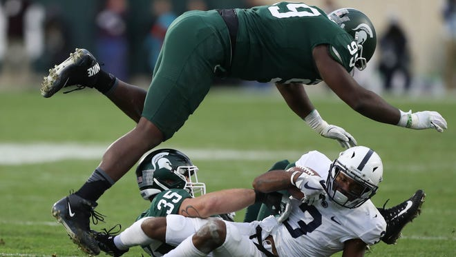 Michigan State's Joe Bachie and Raequan Williams tackle Penn State's DeAndre Thompkins during second quarter action Saturday, November 4, 2017 at Spartan Stadium in East Lansing.