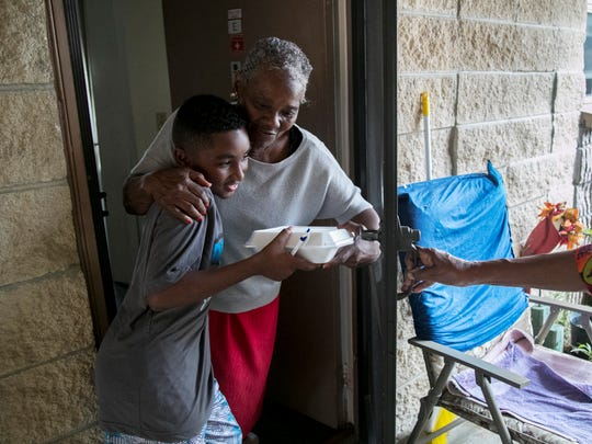 Minnie Ashley gives Ahmir Miller, 10, a hug after he delivered a Christmas meal to her on Saturday, December 17, 2016, at her apartment at Palm City Gardens in Fort Myers.