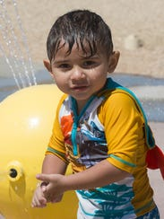 Andres Topete,2, runs around the splash pad at the