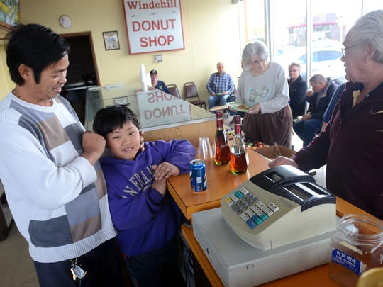 Owner of Windchill Donut Shop San Plong talks with a customer on their last day open Monday, Oct. 26, in Port Huron.