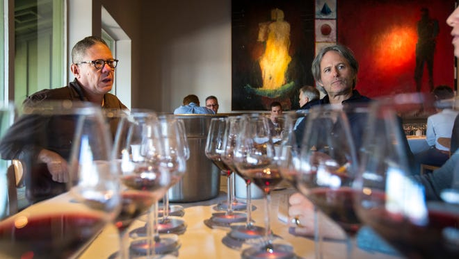 Judges Jeff Grenfell, with Cheuvront, left, and Mark Tarbell listen to other judges in their foursome discuss wine scores at The Arizona Republic Wine Competition at Tarbell's in Phoenix, on Monday, October 27, 2014. Twenty judges each graded 30 wines in the preliminary round, with around 140 Arizona wines competing for top honors.