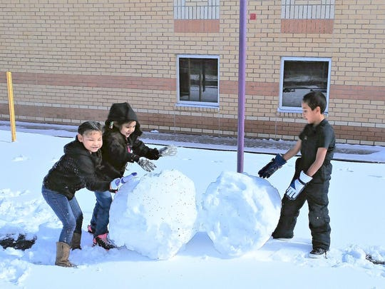 Three first-grade students at Mescalero School have big ideas as they create large balls of snow.