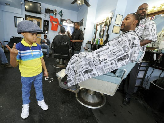 Omar Terell Sr. looks on as his son, Omar Jr., sports Sr.'s hat and flashes a peace sign during a hair cut at Tony Orr Sons & Daughters Barber Shop in York. The talk of the shop Friday was news from Baltimore that six officers were being charged in connection with a man who died in their custody.