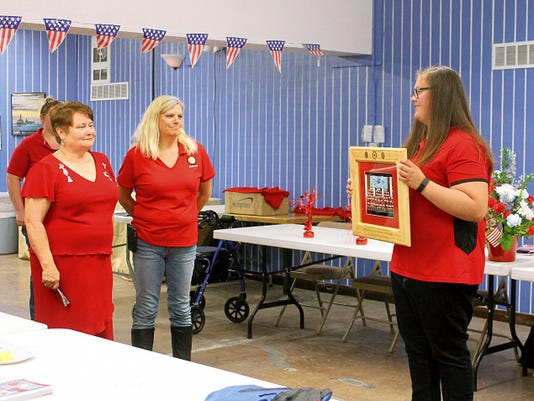 Grace Hendricks presents a custom framed picture of her and the other participants of the American Legion Auxiliary Girls Nation 2015 session to members of Post 34.