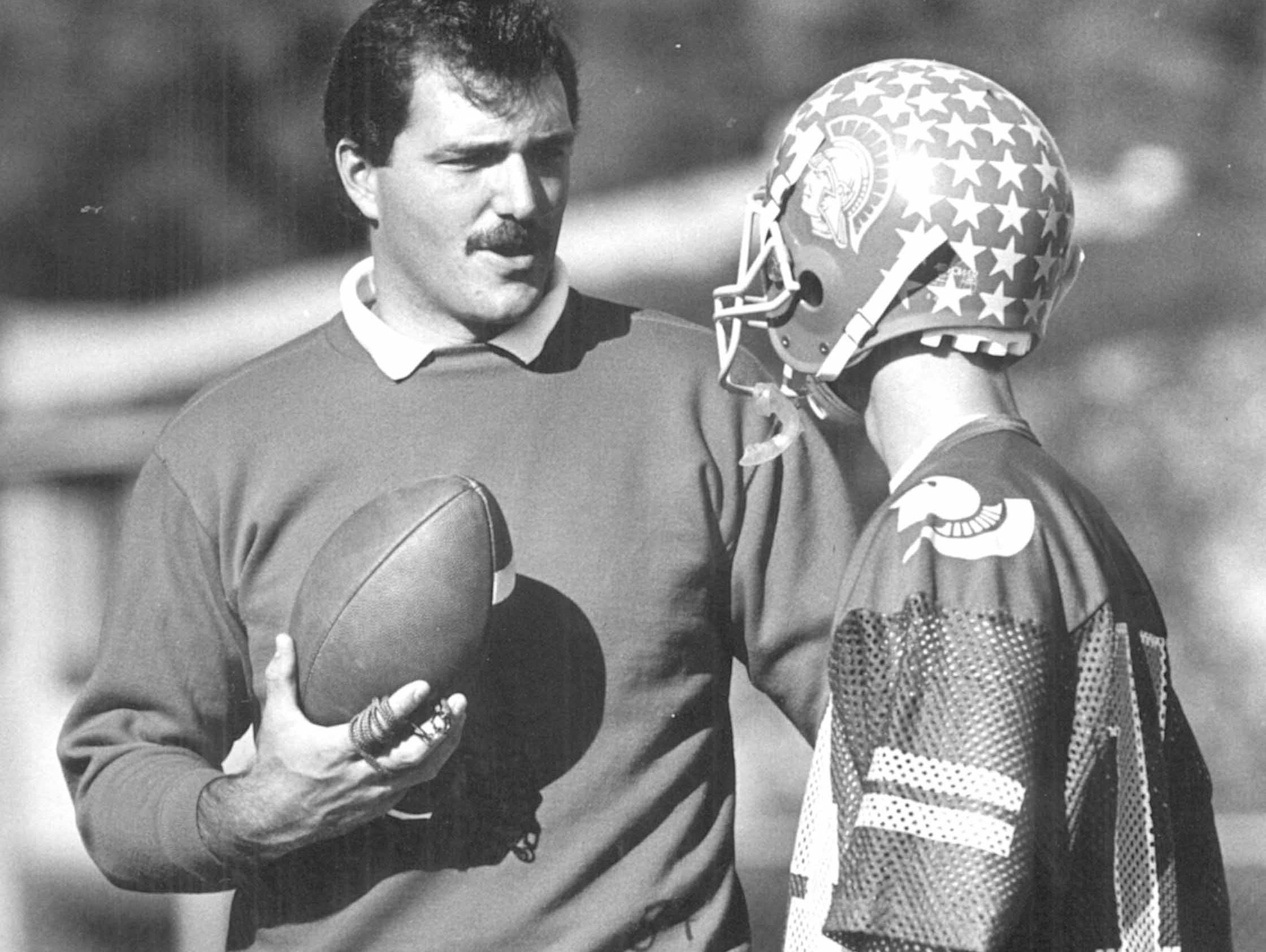 North College Hill coach Bruce Baarendse talking with receiver Rick Kates in 1987.