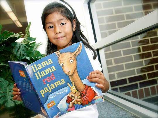 "A young reader with ""Llama, Llama, Red Pajama."" Children's"