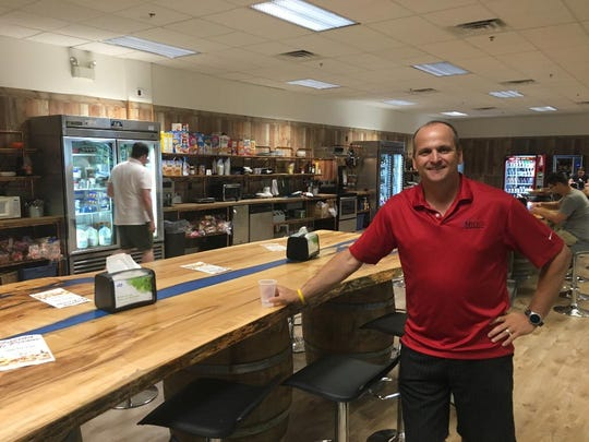 Miles Technologies CEO Chris Miles stands inside of the cafeteria at the company's new location in Lumberton. It's a 163,000 square foot building and they'll use 63,000 square feet for now and rent the rest out. The table he's leaning on is made from an old tree.