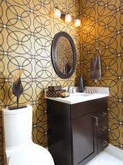 A geometric, Art Deco-inspired wallcovering by Seabrook in the guest bath and powder room brings a feel of Old Hollywood glamour.
