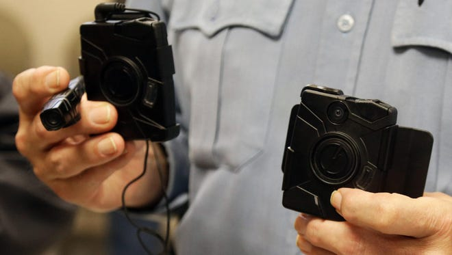 Minneapolis police Lt. G.W. Reinhardt holds two of the body cameras the department will use as part of a pilot program in Minneapolis.