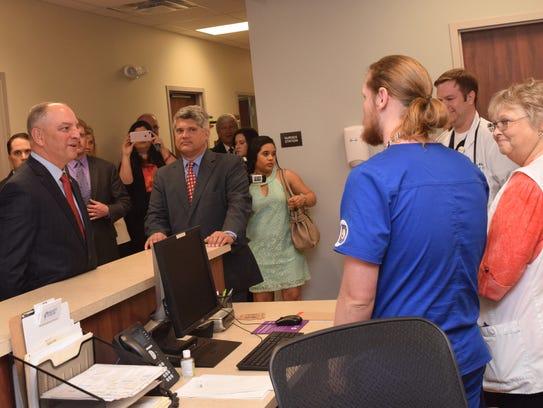 La. Gov. John Bel Edwards (left) talks with staff of