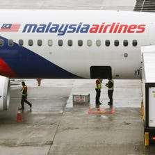 Ground crew stand near a Malaysia Airlines aircraft on the tarmac at the Kuala Lumpur International Airport (KLIA) in Sepang, Malaysia.