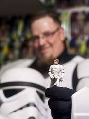 Pat Douglas holds up a figurine of Han Solo dressed
