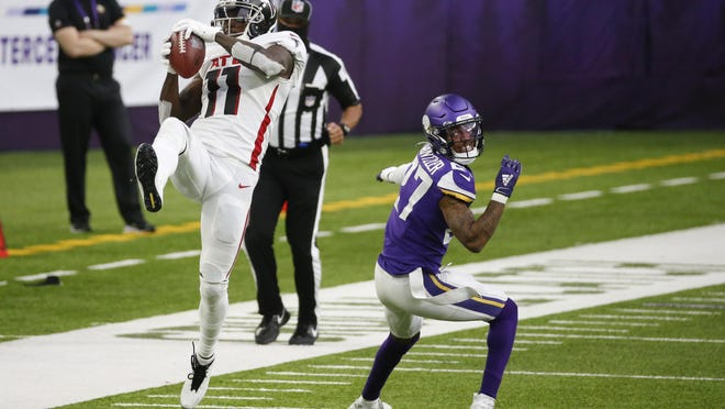 Atlanta Falcons wide receiver Julio Jones (11) catches a pass over Minnesota Vikings cornerback Cameron Dantzler during the second half of an NFL football game, Sunday, Oct. 18, 2020, in Minneapolis.