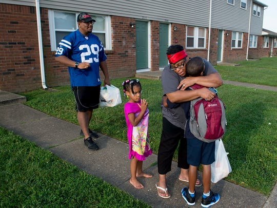 Shannon Higgins gives her third-grader, Jaime Jr., 9, a hug before he walks to school with his dad, Jaime Higgins Sr., for his first day back after summer break Wednesday morning. His sister, Savannah, 3, crawled out of bed to say goodbye to her big brother.