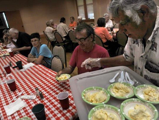 Charles Rener hands Glenn Hamilton ice cream for desert