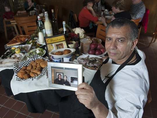 Giovanni (John) Gambino of Gambino's Italian Eatery in Cherry Hill holds up a picture of him and his son Celestino, who died at age 17.