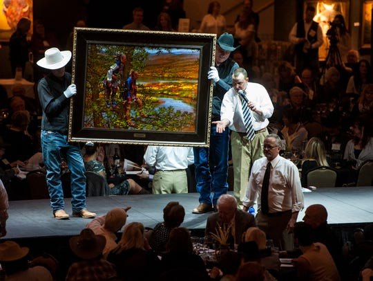 "Auctioneer Troy Black takes bids from the audience for Doug Hall's ""Red Coat Crossing"" during last year's Russell Live Auction."