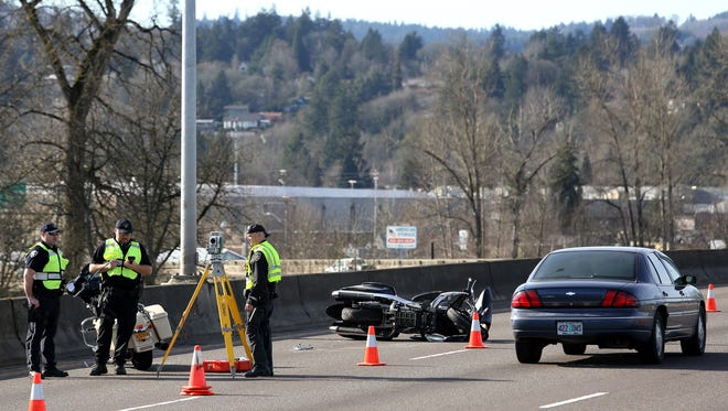 Salem Police investigate a crash on the Marion Street bridge caused a motorcycle driver to be thrown into the Willamette River on Monday, Feb. 16, 2015, in Salem, Ore.