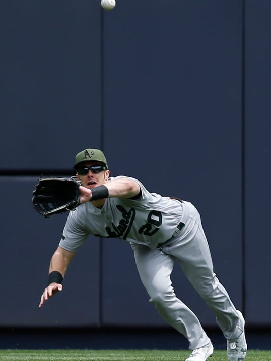 Oakland Athletics center fielder Mark Canha (20) stretches to reach Matt Holliday's first-inning line drive in a baseball game against the New York Yankees in New York, Sunday, May 28, 2017. (AP Photo/Kathy Willens)