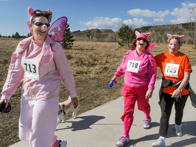 Cindy Leach, Lisa Finley and Carol Felton show off their flying pig outfits as they approach the finish line in the Flying Pig 5k on Sunday, April 6, 2014 at Spring Canyon Park in Fort Collins. The event benefited the Family Support Services Program which provides support to families with a family member with developmental disabilities.
