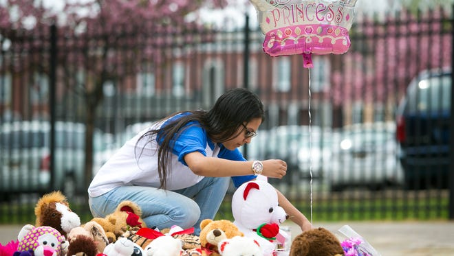 Howard High graduate from 2015, Angeliz Marrero, fixes the balloon as she stops by the make shift memorial in front of Howard High school to show her support for the family of Amy Inita Joyner-Francis.