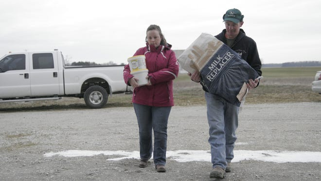 Rose and Greg Hartschuh carry supplies Friday in Lykens Township. The couple has joined forces with more than 50 other local farmers to help gather supplies for ranchers out west who have suffered from recent wildfires.