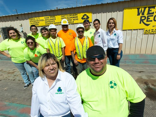 Westside Recycling owners Marilu and Hector Alaniz sit in front of their facility on Tuesday, March 5, 2016, with their team standing behind them. The recycling center is located 8125 Batann Memorial West.