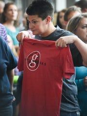 A Garth Brooks fan tries on a Garth shirt at the Denny