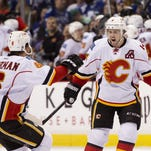 Kris Russell #4 of the Calgary Flames celebrates with Dennis Wideman #6 after scoring what proved to be the game winning goal against the Vancouver Canucks in Game One of the Western Conference Quarterfinals.