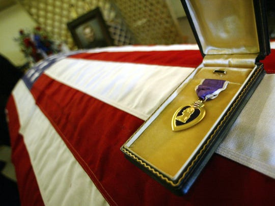 The Purple Heart awarded to Staff Sgt. Dennis Hammond lay on his casket at his funeral service at the Bremond Funeral Home in Robertson County, Texas, in 2004.