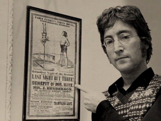 John Lennon poses next to the circus poster that inspired