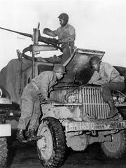 African American members of the World War II Red Ball Express repair a 2½-ton truck while a crewman at a machine gun keeps watch for the enemy.