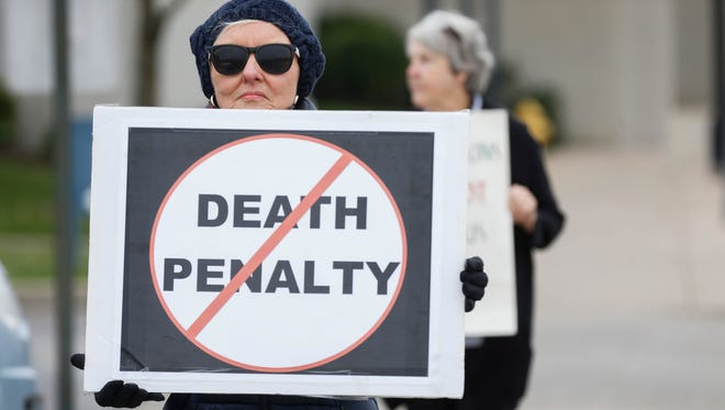 Donna Walmsley, with Missourians for Alternatives to the Death Penalty, carries a sign in front of the Greene County Courthouse during the sentencing phase of the Craig Wood trial on Friday, Nov. 3, 2017.