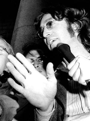 John Lennon talks with reporters following an appearance on Aug. 30, 1974, in a U.S. district court to fight against deportation in New York City.