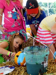 Karley Hull and Olivia Graham paint pumpkins at a festival