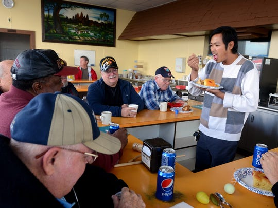 Owner of Windchill Donut Shop San Plong eats some food with some of his regulars on their last day open Monday, Oct. 26, in Port Huron.