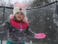 Gracyn Ray, 3, makes jumps on a snowy trampoline at