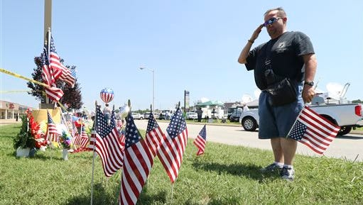 Jonathan Bryan salutes a makeshift memorial on Friday, July 17, 2015 in front of the Armed Forces Career Center off of Lee Highway in Chattanooga, Tenn.  Muhammad Youssef Abdulazeez of Hixson, Tenn., attacked two military facilities on Thursday, in a shooting rampage that killed four Marines. (Dan Henry/Chattanooga Times Free Press via AP)